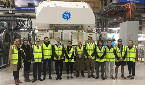 UKNEST Scholars with a Type 26 electric motor at GE Power, Whetstone.  Chair Muir Macdonald (centre) and Vice-Chair Jenny Gardner (far left)
